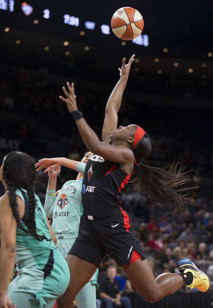 Las Vegas Aces guard Jackie Young (0) drives past New York Liberty guard Brittany Boyd (15) in ...