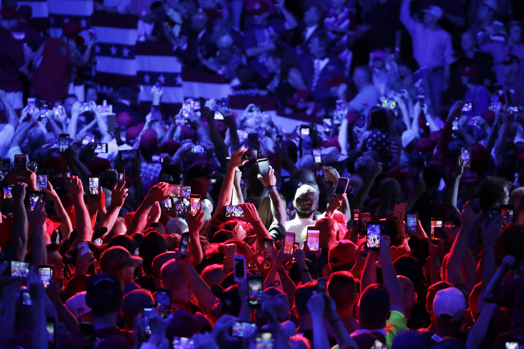 Supporters are bathed in red and blue light as they wait for President Donald Trump to speak at ...