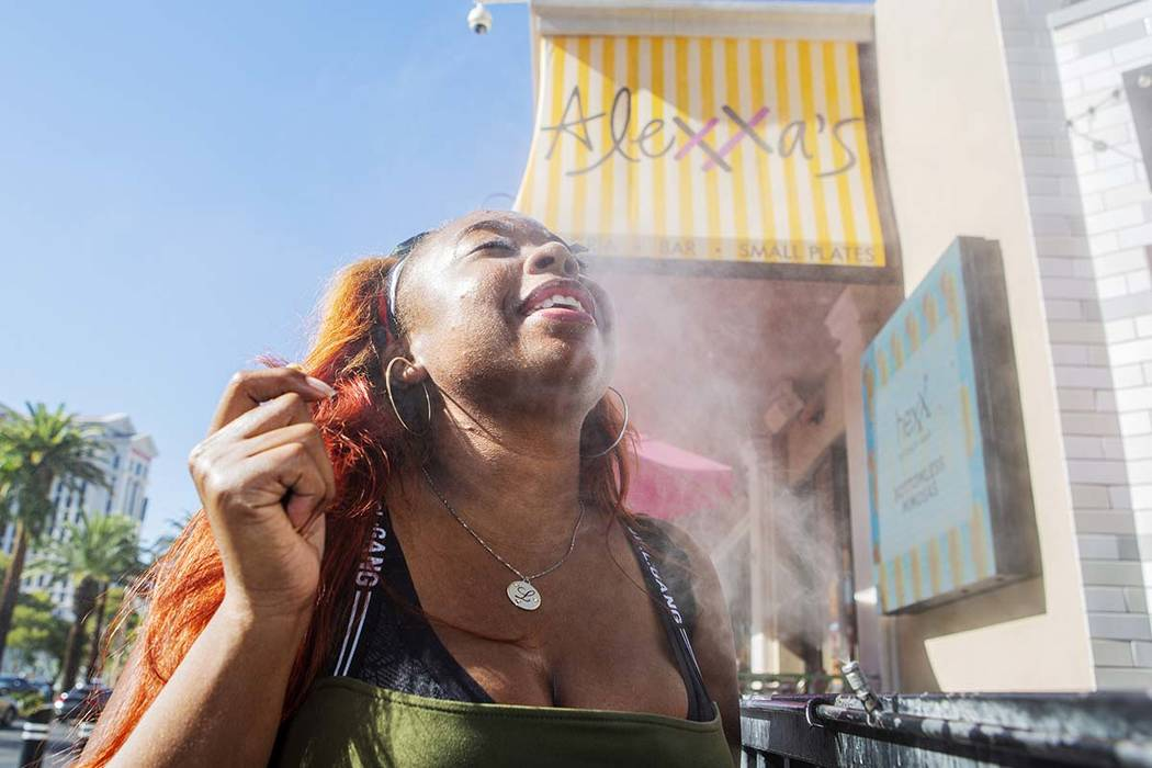 Shelle Ralph from North Carolina cools off from the heat with the water mist outside of Alexxa' ...