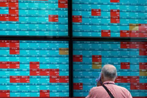 A man looks at an electronic stock board showing Japan's Nikkei 225 index at a securities firm ...