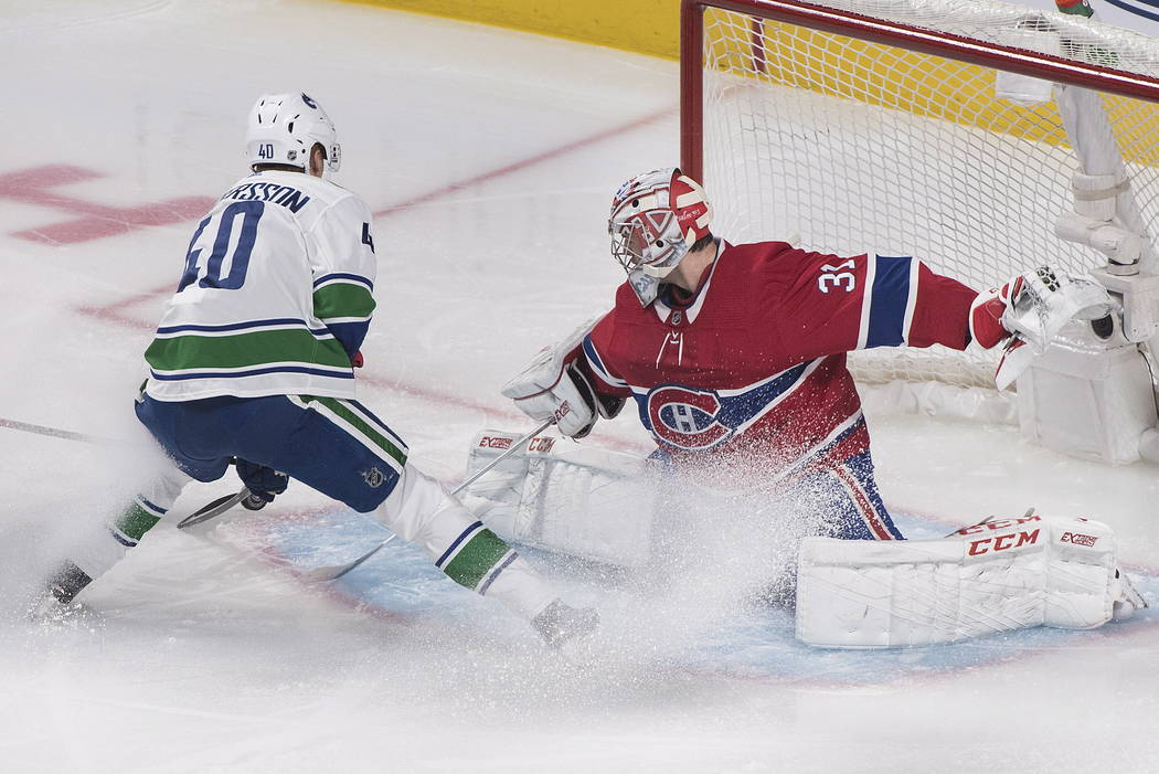Vancouver Canucks' Elias Pettersson moves in on Montreal Canadiens goaltender Carey Price durin ...