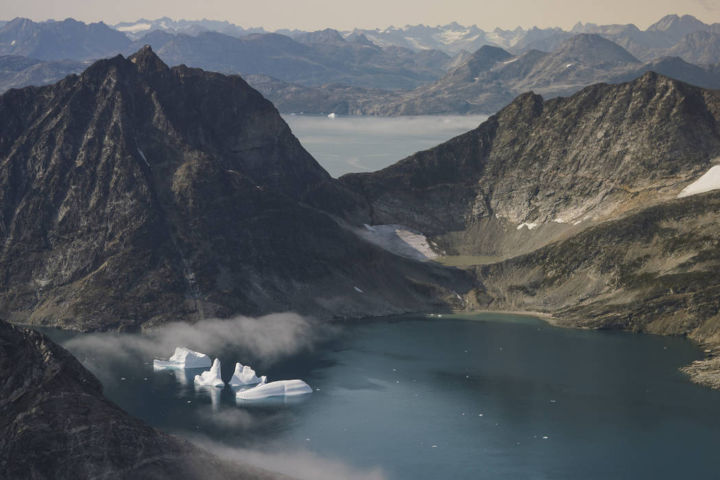 In this photo taken on Wednesday, Aug. 14, 2019, icebergs are photographed from the window of a ...