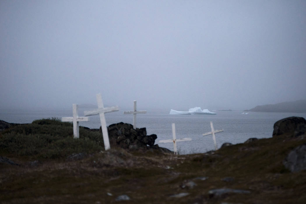 An iceberg floats near a cemetery in Kulusuk, Greenland, early Thursday, Aug. 15, 2019. Greenla ...
