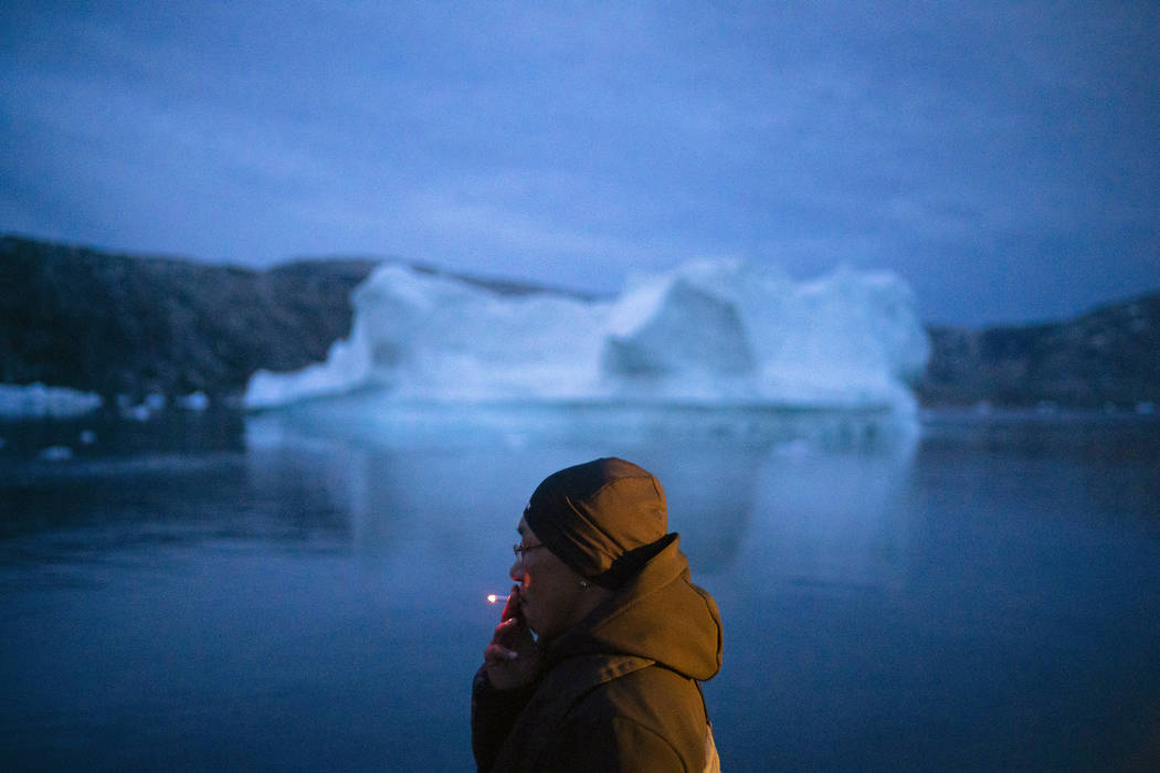 A local man smokes a cigarette as he rides on a boat past icebergs in eastern Greenland, late F ...