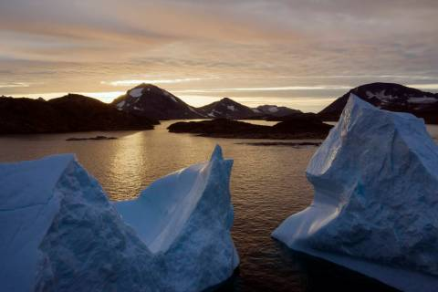 An aerial view of large Icebergs floating as the sun rises near Kulusuk, Greenland, early Frida ...
