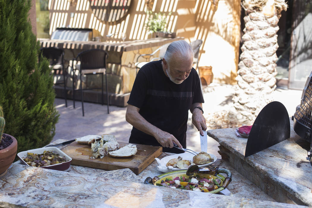 Hubert Keller, chef of Fleur de Lys and Fleur, cuts a rotisserie chicken in his backyard kitche ...