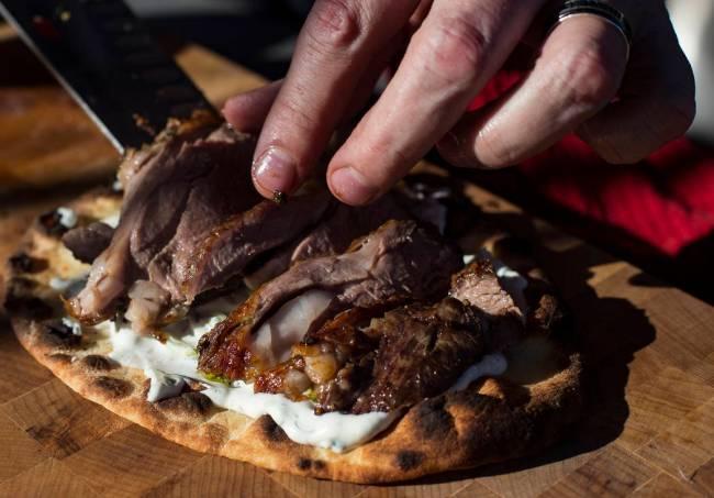 Matt Silverman, chef for HEXX Kitchen + Bar, prepares rotisserie lamb on flat bread with tzatzi ...