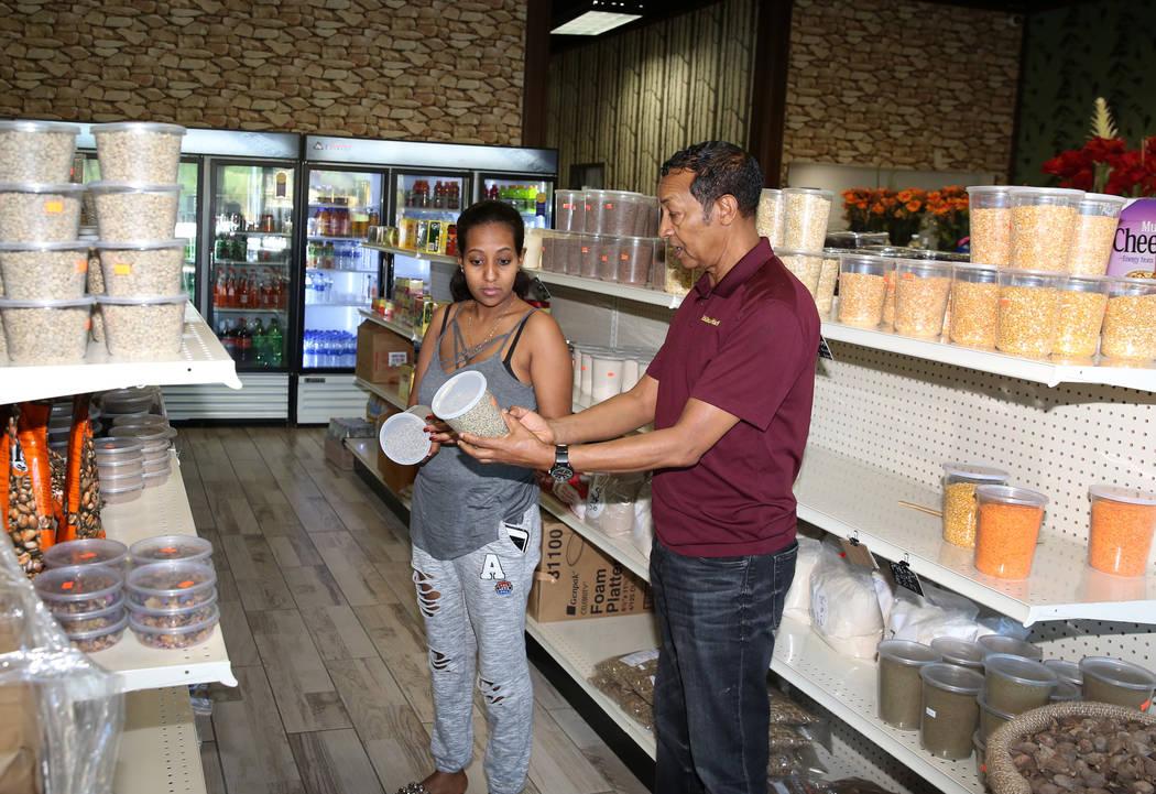Legesse Tigabu, right, owner of Melkam Market, an Ethiopian store, assists his customer Mesrak ...