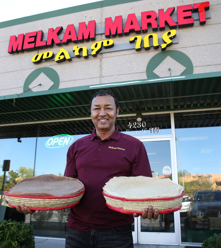 Legesse Tigabu, owner of Melkam Market, an Ethiopian store, poses for photo holding authentic I ...