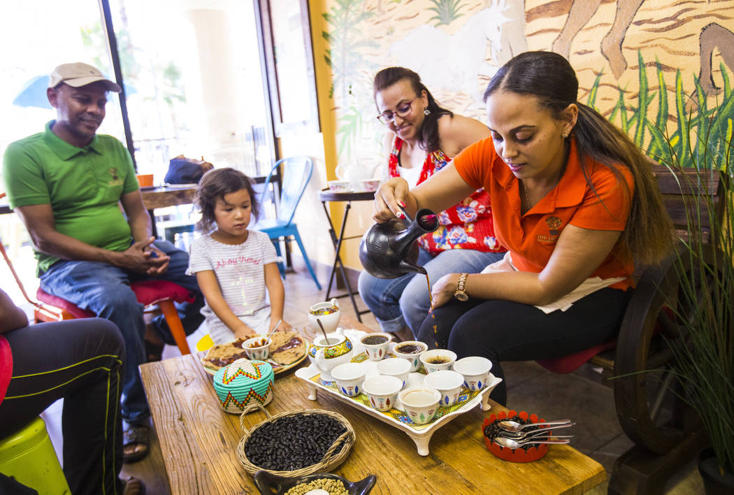 Gio Marongiu, store manager at Java Tree, right, pours coffee in a traditional Ethiopian coffee ...