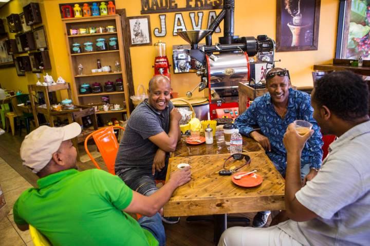 Solomon Teklu, owner of Java Tree, left, talks with his customers including Mekonnen Gebremedhi ...