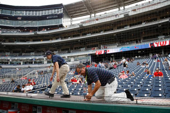 Workers adjust new netting that separates the infield from lower bowl seating beforea basebal ...