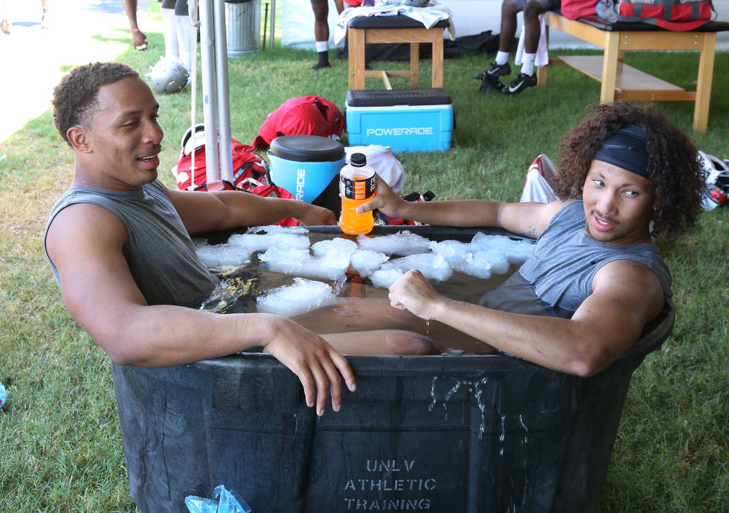 UNLV's linebacker Tre Caine, left, and defensive back Greg Francis, cool off in an ice bath aft ...