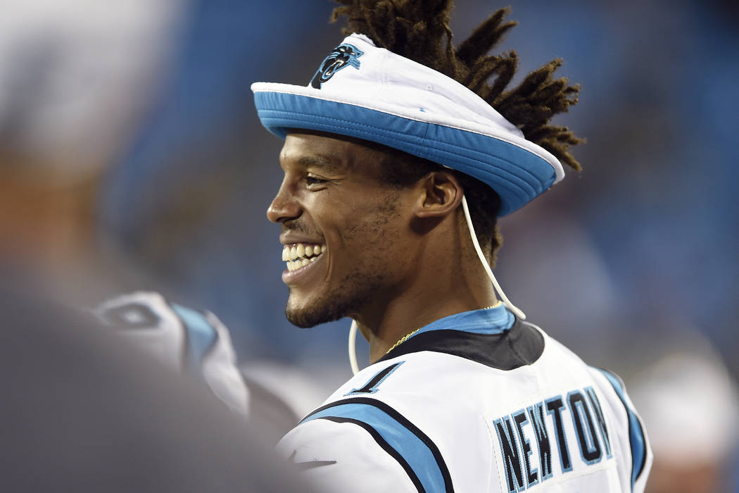 Carolina Panthers quarterback Cam Newton smiles from the sidelinesduring the second half an NFL ...