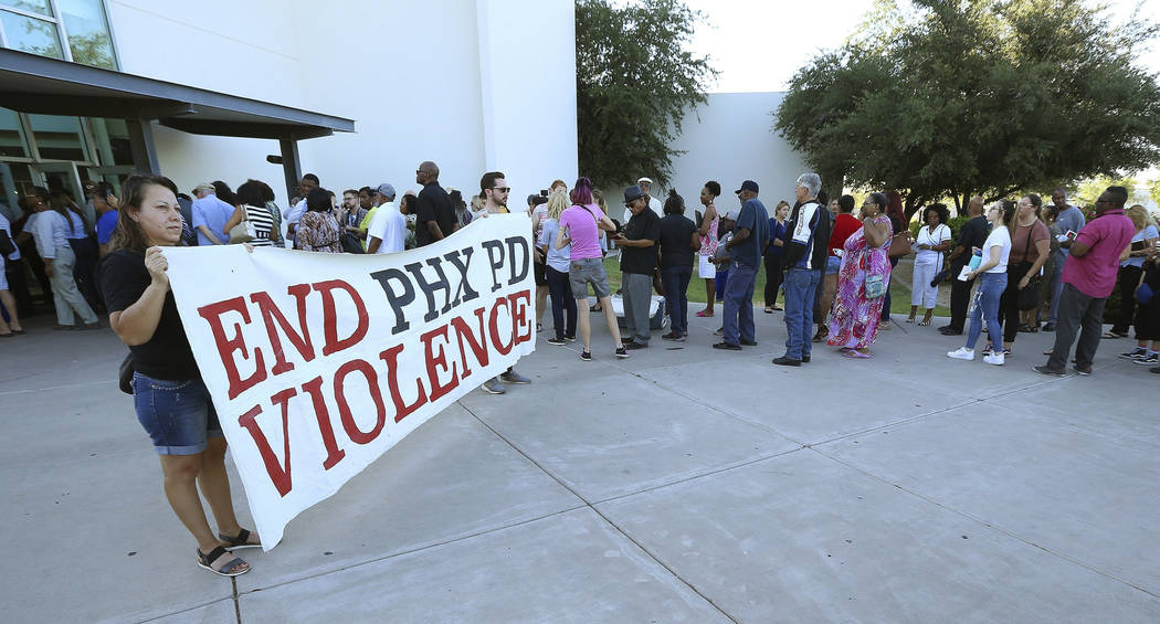 In this June 18, 2019 file photo people line up near protesters outside a venue for a community ...