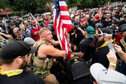 "Joseph Oakman and fellow Proud Boys plant a flag in Tom McCall Waterfront Park during an "" ..."
