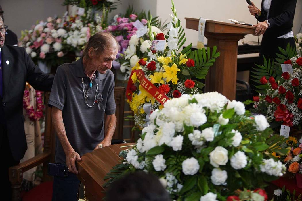 Antonio Basco, companion of Margie Reckard, leans on her casket during her funeral at La Paz Fa ...
