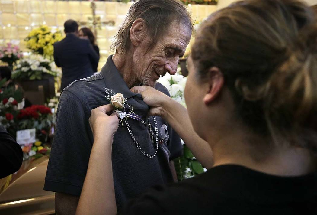 Antonio Basco has a flower pinned to his shirt at the funeral of his companion of 22 years, Mar ...