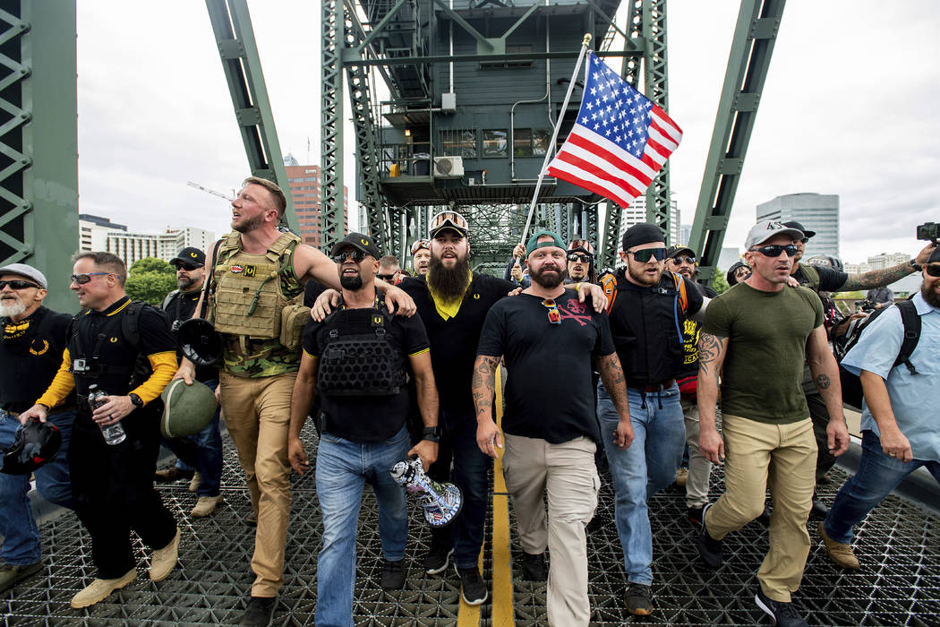 Members of the Proud Boys and other right-wing demonstrators march across the Hawthorne Bridge ...