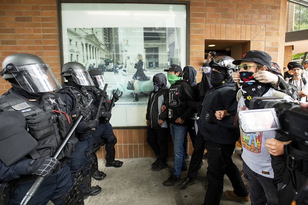 Police officers face off against protesters opposed to right-wing demonstrators following an &q ...