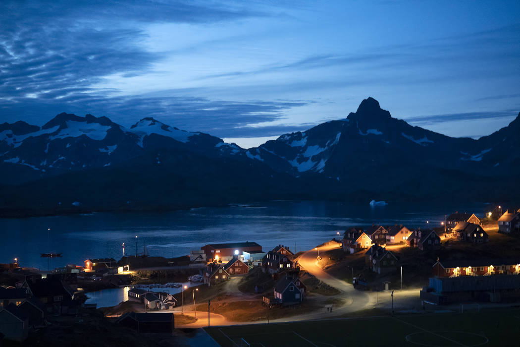 In this photo taken late Friday, Aug. 16, 2019, homes are illuminated after the sunset in Tasii ...