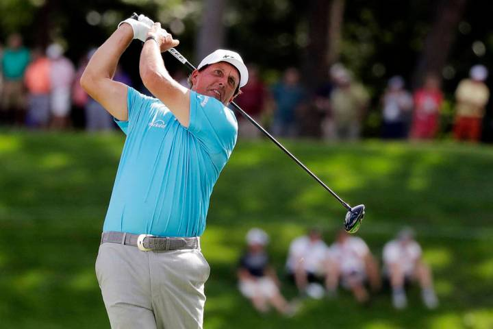 Phil Mickelson watches his tee shot on the 18th hole during the second round of the BMW Champio ...