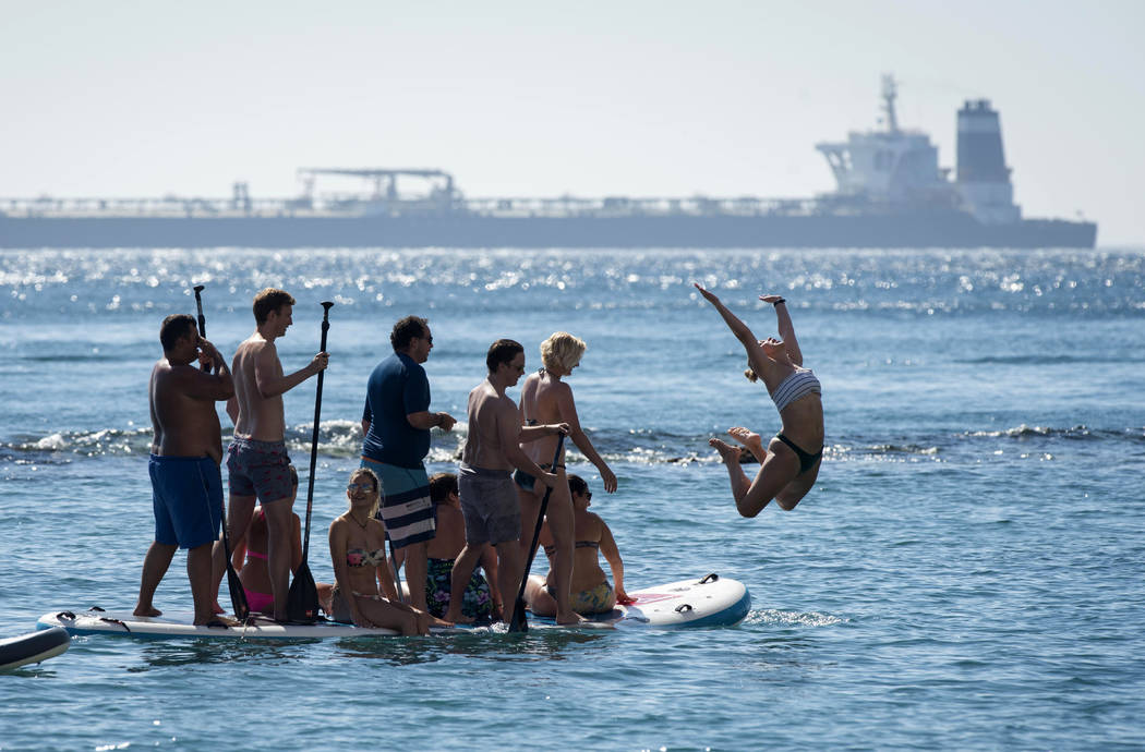 Renamed Adrian Aryra 1 super tanker is seen in background as people cool-off in the water in th ...