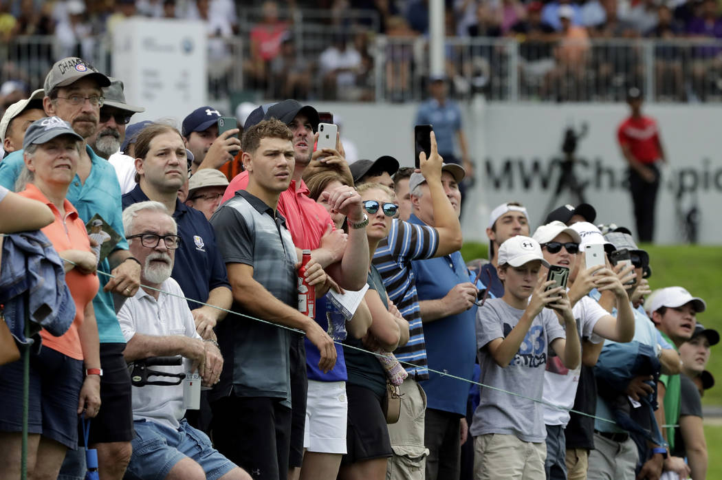 Fans watch Tiger Woods' tee shot on the 13th hole during the final round of the BMW Championshi ...