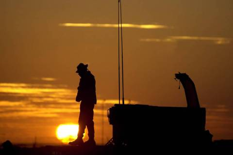 The sun sets on an American soldier at the Kandahar airport in Afghanistan in 2001. (AP Photo/E ...