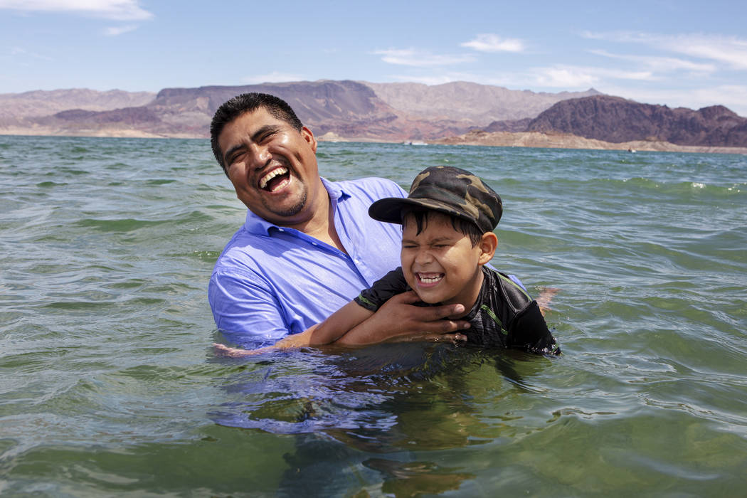 Pastor Erasmo Solis laughs while teaching his son Girsom Solis how to swim at Boulder Beach on ...