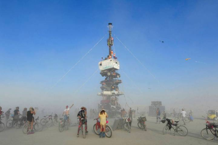 """Burners are surrounded by playa dust climb onto an art installation titled, """"Night of the Climb ..."""