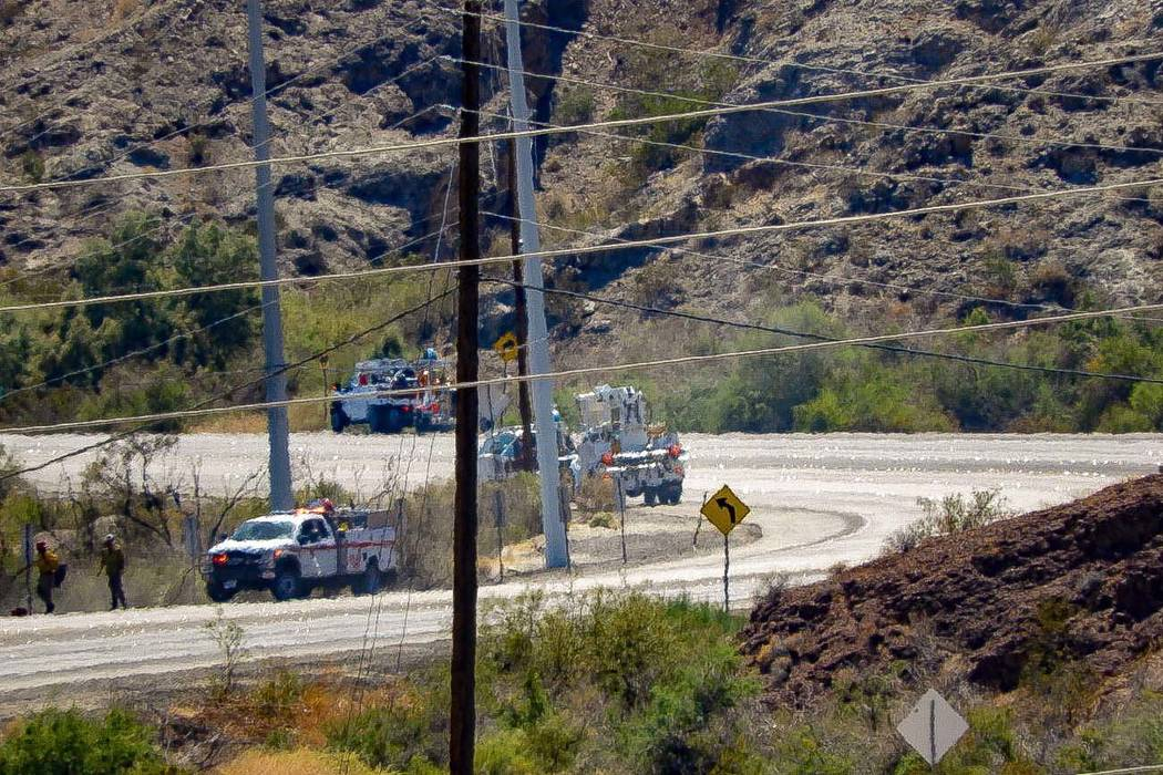 Crews make repairs to power lines in a burned area from the fire at Big Bend of the Colorado St ...