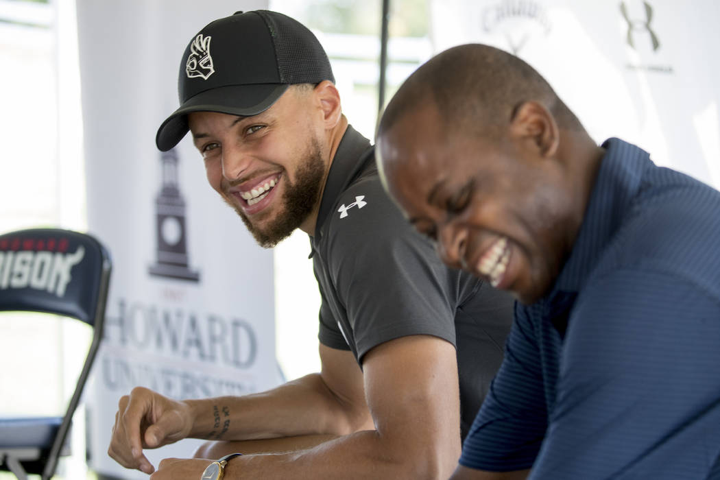 Golden State Warriors guard Stephen Curry, left, and Howard University president Wayne Frederic ...
