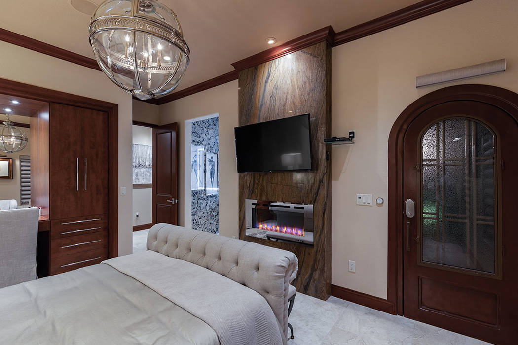 The master bedroom has a modern fireplace. (David Reisman Real Estate Millions)