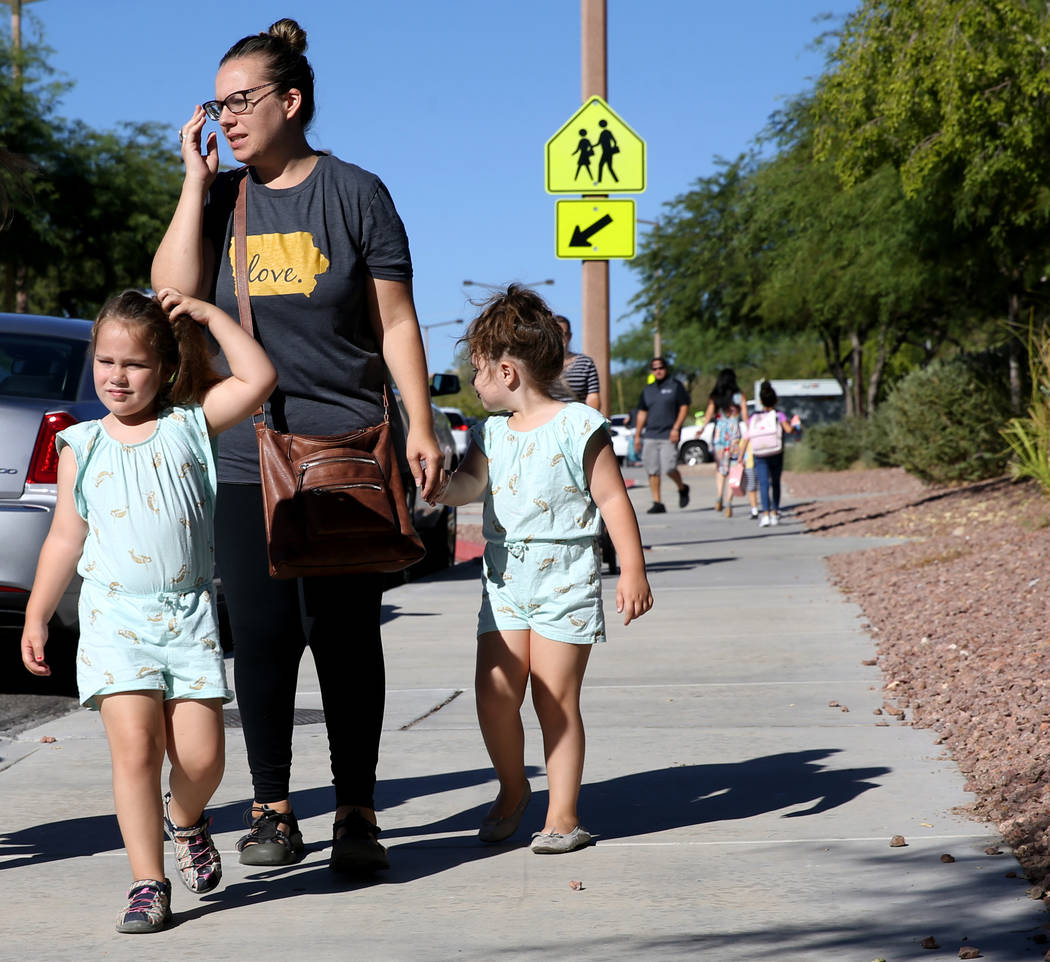 Melissa Kendal talks to a reporter with her twins Lucie and Charlotte, 4, at Staton Elementary ...