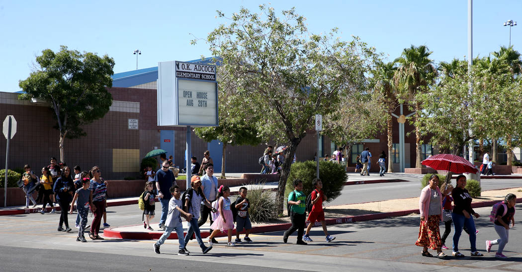 Parents walk their children home from Adcock Elementary School in Las Vegas Tuesday, Aug. 20, 2 ...