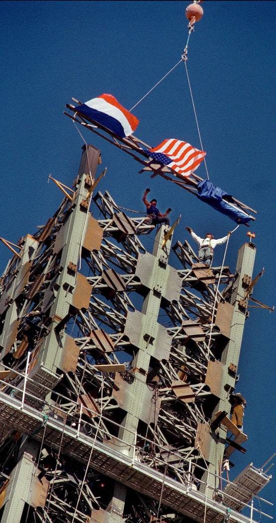 Iron workers topped off the Eiffel Tower at Paris-Las Vegas with a final, flag-fastened beam on ...