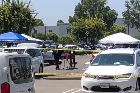 Orange County coroners remove a body of a stabbing victim from a parking lot from a parking lot ...