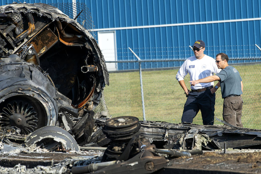 Members of the National Transportation Safety Board looks at the wreckage of a plane that Dale ...