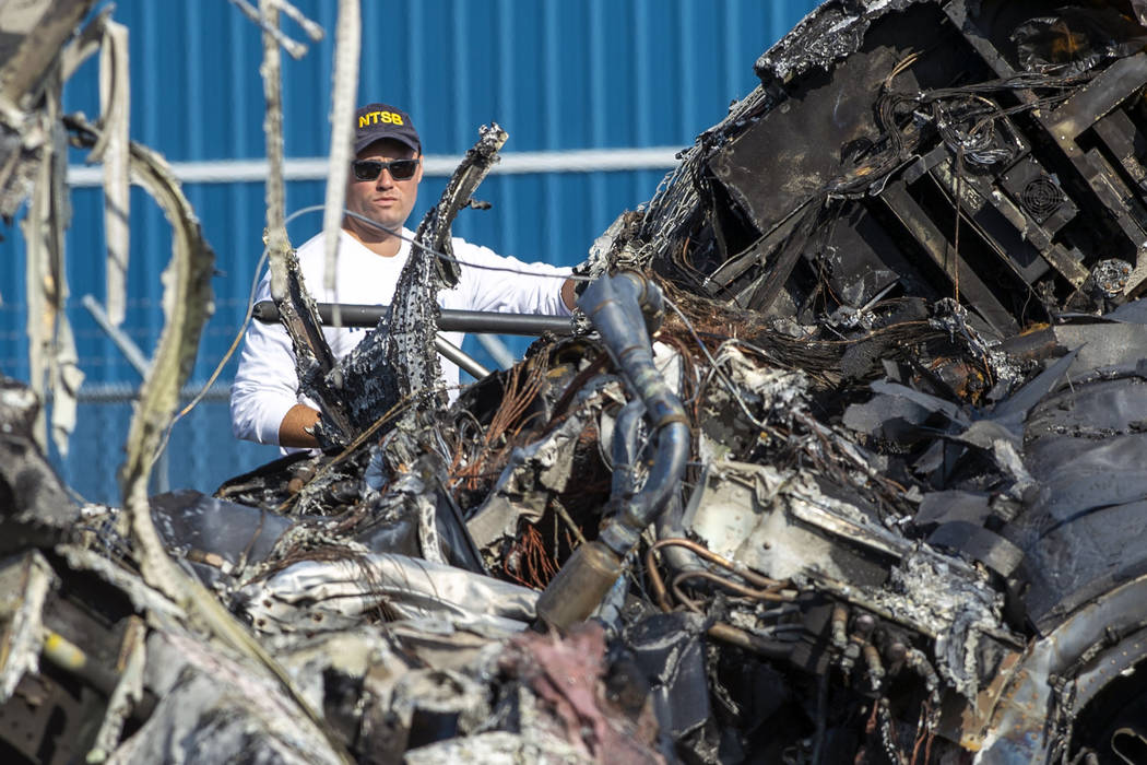 A member of the National Transportation Safety Board looks at the wreckage of a plane that Dale ...