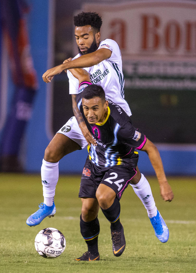Las Vegas Lights FC forward Jose Villarreal (24) advances the ball while fighting off Portland ...