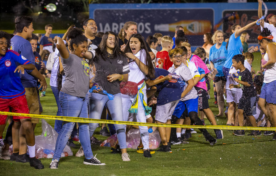Las Vegas Lights FC fans enjoy a massive water balloon fight on field at halftime during their ...
