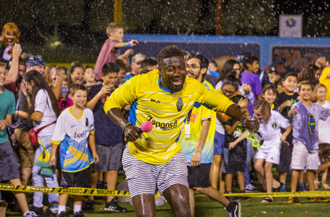 Las Vegas Lights FC hype man Bojo Ackah is pelted as he escapes the fans on field during a mass ...