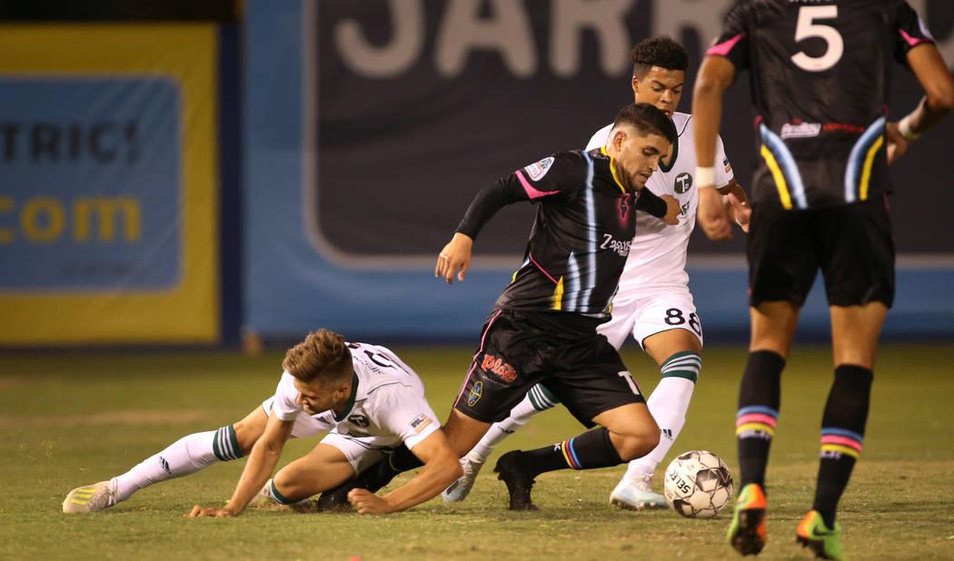 Las Vegas Lights FC forward Irvin Parra (11, center) is taken down by Portland Timbers 2 forwar ...