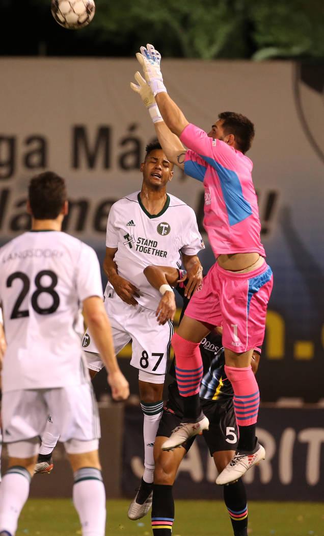 Las Vegas Lights FC goalkeeper Thomas Olsen (1, right) pulls in a header from a Portland Timber ...