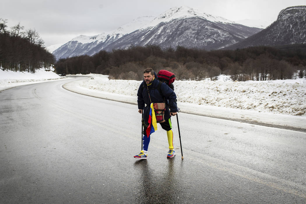 Venezuelan Yeslie Aranda, 57, walks on Route 3 between Tolhuin and Ushuaia, Argentina, Saturday ...