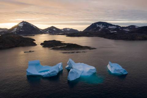 In an Aug. 16, 2019, photo, large Icebergs float away as the sun rises near Kulusuk, Greenland. ...