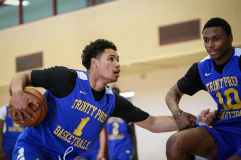 Trinity International junior Daishen Nix (1) drives against teammate Marlon Lestin during a pra ...