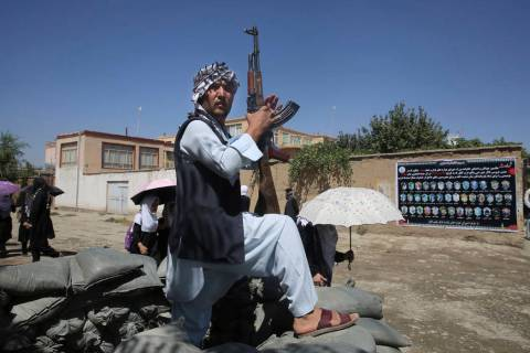 An Afghan volunteer stands guard outside a mosque during a memorial service for the victims of ...