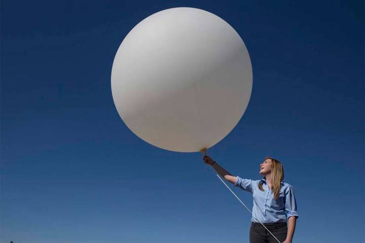 Meteorologist Chelsea Kryston prepares to launch a balloon carrying a radiosonde that collects ...